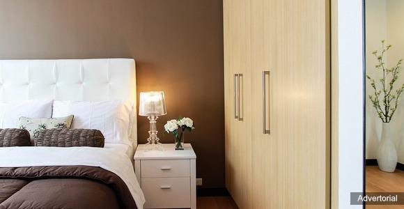 En seng i et flot og arkitektonisk soveværelse.